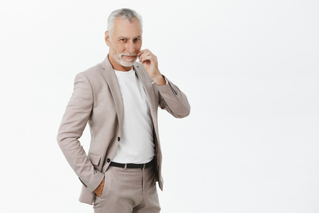 Handsome charismatic senior businessman rolling moustache with fingers, smirking with delight and self-assured expression holding hand in pocket standing in confident pose over grey wall wearing suit