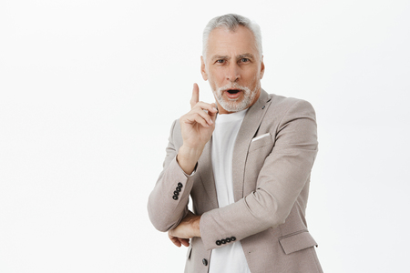 Portrait of creative smart and fancy good-looking senior male entrepreneur raising index finger in eureka gesture crossing hand over chest adding suggestion having idea over gray background