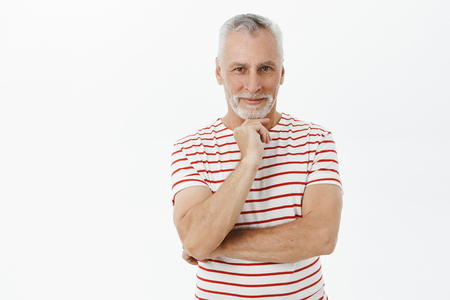 Charming happy and enthusiastic old man with white hair and beard in cute striped t-shirt smiling joyfully holding hand on chin in thoughtful pose and gazing at camera having interesting idea Reklamní fotografie