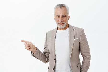 Waist-up shot of handsome self-assured charismatic grandfather in elegant suit with beard and grey hair pointing left smiling with confident and assured expression posing over white background Reklamní fotografie