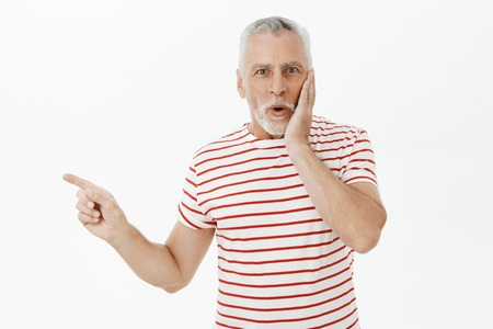 Portrait of surprised and shocked charming impressed senior man with beard and grey hair pressing hand to cheek in amazement saying wow pointing left intrigued and astonished over white wall