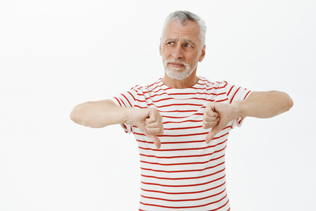 Old man giving negative feedback to place he visited. Portrait of displeased and unimpressed handsome senior bearded man in striped t-shirt showing thumbs down and looking left disappointed Stockfoto