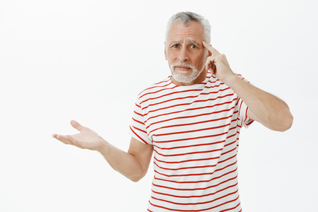 Are you out of your mind. Upset mature dad with white hair and beard in striped t-shirt raising palm in clueless gesture rolling index finger on temple being disappointed in person acting crazy