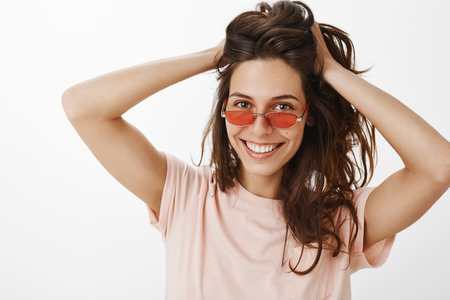 Portrait of stylish cheerful party girl in red sunglasses touching and playing with beautiful natural hair combing it as smiling broadly at camera posing against gray background joyful and confident Stock fotó