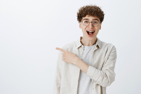 Handsome young man with curly hairstyle and round glasses smiling happy and energized as pointing left and asking question about awesome copy space posing delighted and amused over gray background