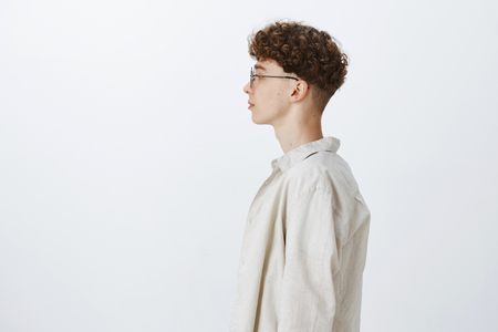 Profile shot of stylish handsome young hipster male freelancer with curly hairstyle in glasses looking left and standing casually over gray background in shirt, having no emotions as feeling calm