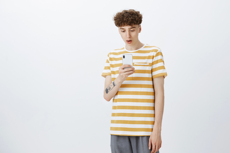 Portrait of shocked guy being surprised cool chick swiped him in date app dropping jaw staring impressed at smartphone screen as standing speechless over gray background in striped t-shirt and pants