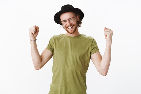 Waist-up shot of delighted successful male in glasses and hat yelling yes proudly as clenching raised fists in victory and triumph gesture smiling being excited from win, cheering over gray background