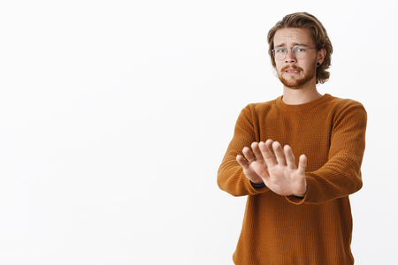 Wow no thanks stay back. Disgusted and intense displeased european guy pulling hands towards camera waving in no and rejection gesture clenching teeth from aversion and dislike over gray wall Stock Photo