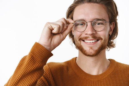 Close-up shot of satisfied accomplished and smart bearded ginger guy in sweater touching glasses and smiling broadly with friendly grin, standing confident and joyful over gray background 免版税图像