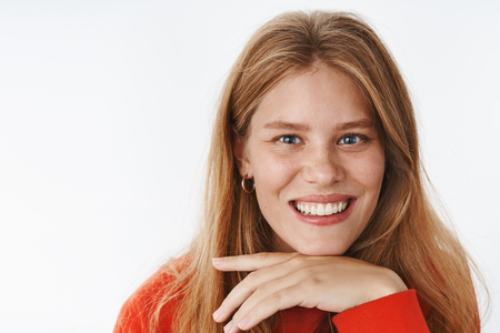 Headshot of happy charismatic attractive caucasian girl with fair hair, freckles and deep blue eyes gazing at camera interested and joyful leaning head on palm as if listening, smiling broadly Stock Photo