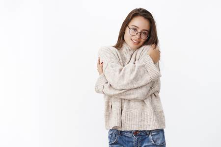 Cute and tender girlfriend in glasses hugging herself and leaning head on shoulder as feeling lonely, missing boyfriend on cold winter day, wearing warm sweater to feel comfort over gray background Stock Photo