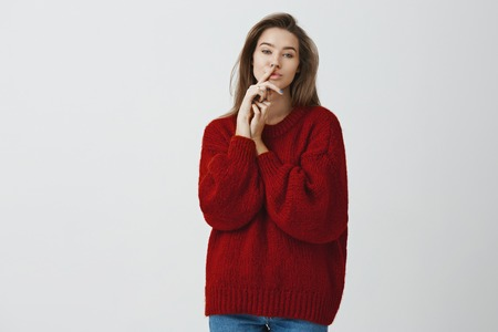 Sensuality, feminine and beauty concept. Portrait of charming flirty and sassy young sexy woman in red loose winter sweater holding index finger on lips hiding cheeky secret, shushing over white wall