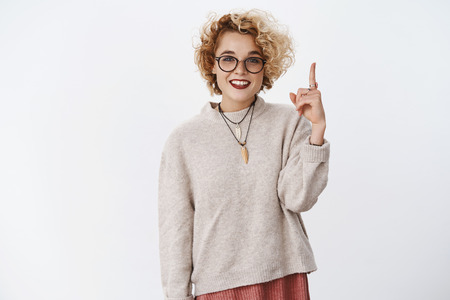 Have you seen this product. Portrait of happy enthusiastic and carefree young beautiful woman in glasses with short blond curly hairstyle raising index finger pointing up, directing upwards Foto de archivo