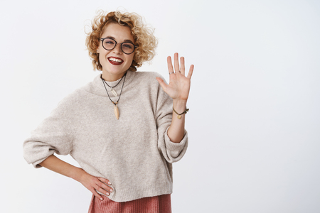 Hello how are you. Portrait of friendly-looking charming cheeful woman with blond short hair in glasses and pleasant gaze waving raised palm in hi, greeting or goodbye gesture smiling at camera
