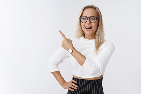Woman panicking got no time, deadling concept. Portrait of freaked out nervous and anxious young attractive funny woman in glasses pointing at upper left corner worried open mouth frowning upset