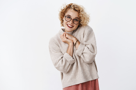 Girlfriend impressed her on valentines day. Portrait of cute charming and caring queer girl with blond hair and piercing in sweater clap hands and smiling lovely as receiving cute gift over white wall
