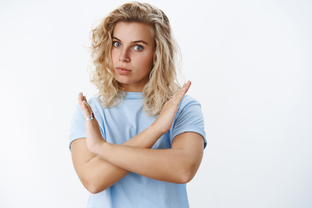 Portrait of serious-looking displeased and intense bossy blond female with short curly haircut and blue eyes expressing disagreement showing cross gesture in prohibition