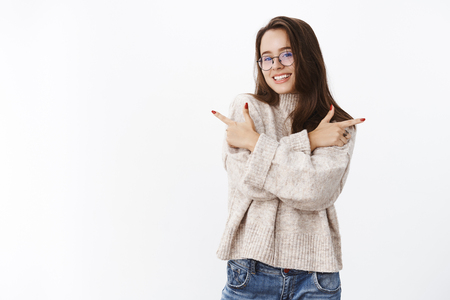 Indoor shot of happy pretty brunette in glasses and warm sweater crossing arms over chest, pointing left and right, smiling broadly as showing opportunities, variety of products over gray background