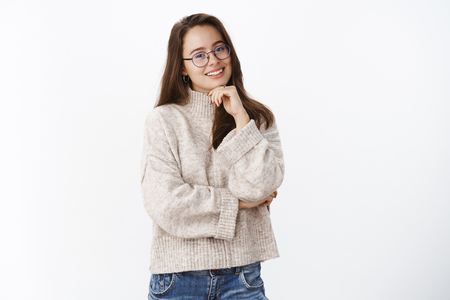 Waist-up shot of happy charismatic young brunette in glasses and warm sweater tilting head and smiling holding hand on chin, crossing arm against chest having conversation over gray background