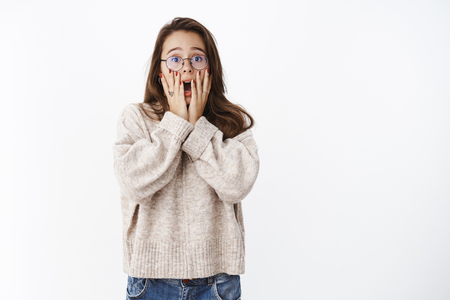 Indoor shot of freaked out shocked and amazed young woman in glasses and sweater shouting from shook covering opened mouth with hands, being scared and insecure, standing intense over gray wall