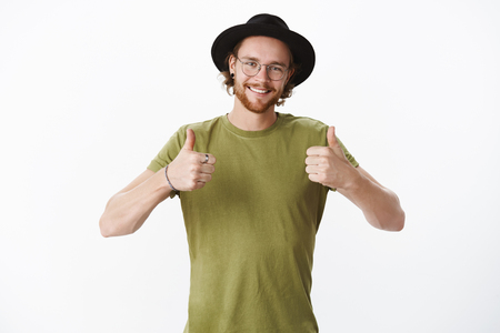 Portrait of satisfied and happy young impressed bearded male in glasses, hat and piercing showing thumbs-up in approval and like, giving positive feedback over gray wall