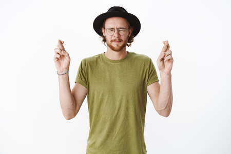 Waist-up shot of intense hopeful european young handsome guy with closed eyes in glasses and hat crossing fingers for good luck, making wish putting effort to pray over gray background Reklamní fotografie