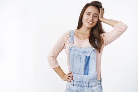Indoor shot of attractive brunette girlfriend in denim overalls playing with hair and holding hand on hip as smiling broadly at camera making cute gazes, flirting over gray background