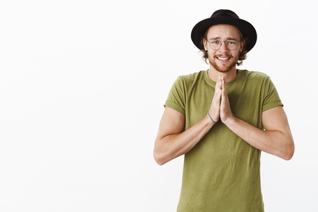 Portrait of intense begging cute sincere young bearded male in glasses and hat asking help or lend money clenching teeth in sorry smile frowning holding hands in pray
