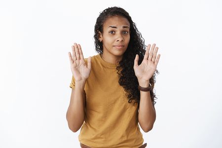 Uninterested african-american female friend raising palms in surrender as giving rejection or refusal, shaking head in no and stepping back over gray background