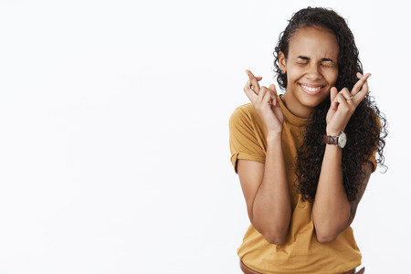 Hopeful and optimistic happy thrilled african-american girl crossing fingers with excitement and happiness as making wish for good luck, praying with smile and closed eyes