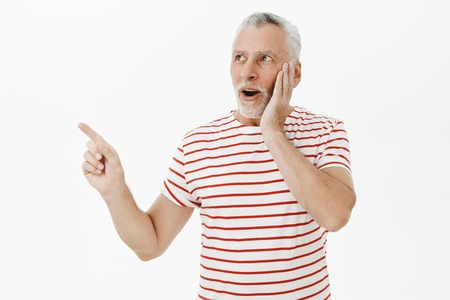Surprised and amused expressive good-looking senior bearded male with grey hair in striped cute t-shirt gasping amazed touching cheek looking and pointing at upper left corner impressed