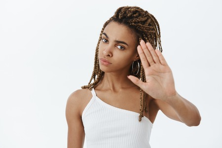 Confident serious-looking displeased and annoyed african american woman with dreadlocks raising palms to decline and say no demanding person stop shooting being irritated over gray wall Stock Photo