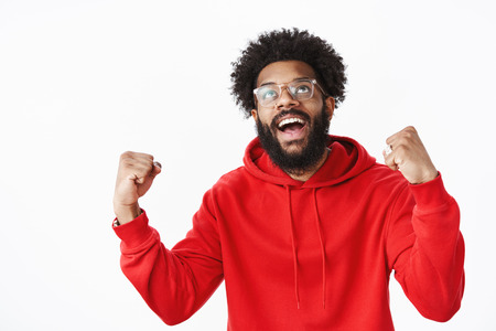 Delighted and relieved african american man with beard in red hoodie raising fists in success celebrating victory