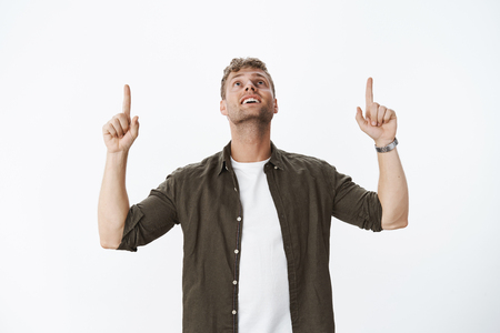 Portrait of fascinated and charmed amazed attractive blond guy with bristle smiling delighted raising head as looking impressed and happy up, pointing upwards over grey wall Stock Photo