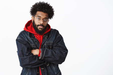 Intense attractive african american guy with beard and afro hairstyle in denim jacket .