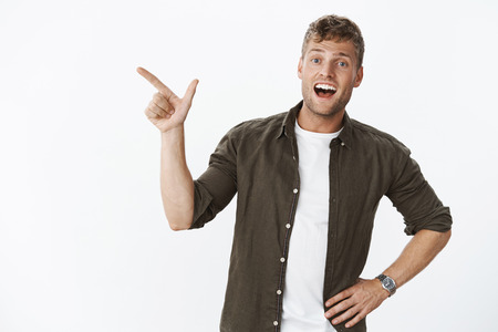 Portrait of surprised excited happy good-looking european blond guy with bristle wearing watch, smiling delighted and impressed as pointing at upper left corner over grey wall