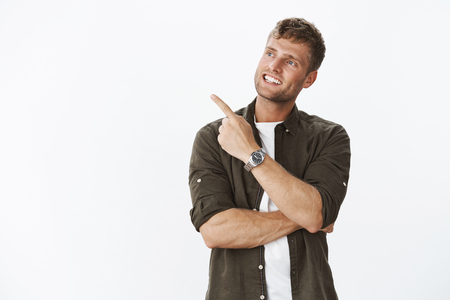 Waist-up shot of satisfied dreamy and happy handsome blond man with bristle and charming smile pointing. Stock Photo