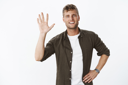 Relaxed and carefree friendly young masculine sportsman raising palm as giving high five or saying hello.