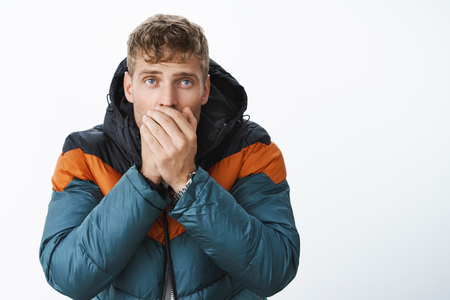 Handsome blond man with blue eyes exhaling air in palms to warm-up standing in stylish puffer jacket outside, freezing, feeling cold during bad winter weather, trembling over gray background