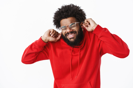 African american bearded guy in red hoodie grimacing, close eyes intense and clenching teeth as preparing to loud noise or sound of siren. Stock Photo