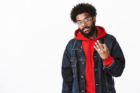 Cool and stylish urban african american guy in glasses, rings and denim jacket over hoodie with pierced nose and afro hairstyle showing number three with fingers as making order over gray wall