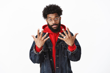 Portrait of cool and stylish african-american modern guy with beard, afro hairstyle and pierced nose showing number ten or dozen with raised palms, waiting for money, posing against gray background