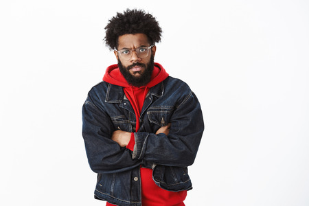 Portrait of annoyed and angry handsome african-american stylish bearded man with glasses and pierced nose frowning crossing arms over chest in insulted pose, being gloomy as friend tricked him