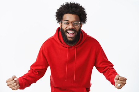 Indoor shot of confident and optimistic african american bearded man in glasses and red hoodie bending towards camera supportive, clenching fists in cheer and smiling broadly being fan over gray wall