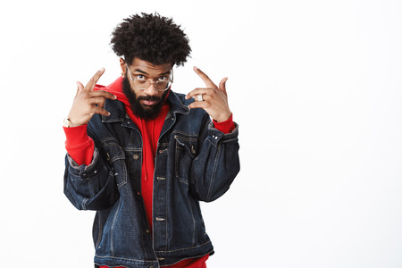 Indoor shot of popular and stylish handsome african american hipster in denim jacket over hoodie showing victory signs looking from under forehead cool and confident posing over gray background