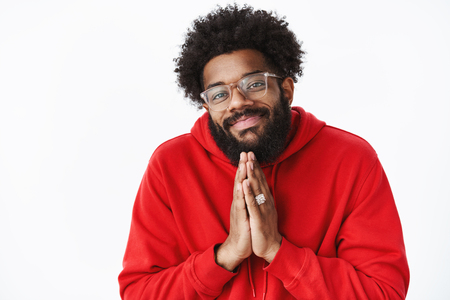 Chill and carefree friendly-looking african american male with beard in glasses making angel look as holding hands in pray and begging for favour or showing namaste welcome gesture over gray wall