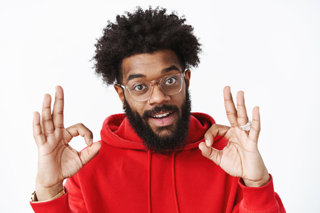Satisfied and delighted outgoing african american bearded man in glasses with afro hairstyle wearing red hoodie showing okay gesture in approval.