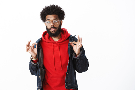 Portrait of calm good-looking stylish african-american male with beard, pierced nose and afro haircut showing okay gesture with orbs and looking careless.