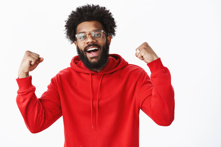 Guy feeling awesome, winning, celebrating victory raising fists in triumph and success smiling broadly as in good mood, standing upbeat in red hoodie over gray background, achieving great result